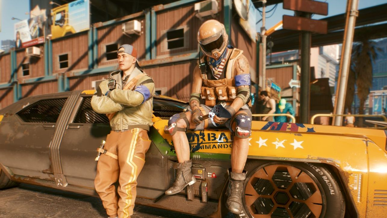 A screenshot of two lads sitting on/leaning against a futuristic yet grimy race car. One of them is holding a Cyberpunk 2077 wireless controller casually in his hand