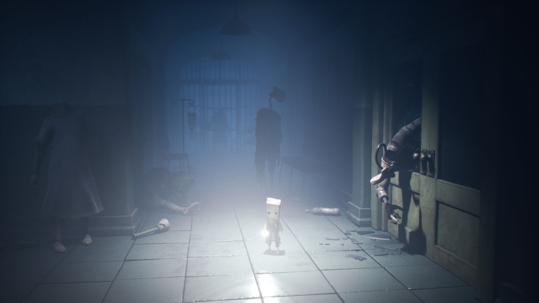 Mono in Little Nightmares standing in a corridor in what looks like a hospital. There are several mannequin figures in the corridor. One has half broken through a doorway on Mono's right, in an effort to grab him