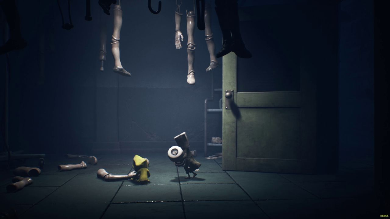 A screenshot from Little Nightmares 2 showing Mono running towards Six, the protagonist from the previous game. She is sitting on the floor playing with a dummy arm.
