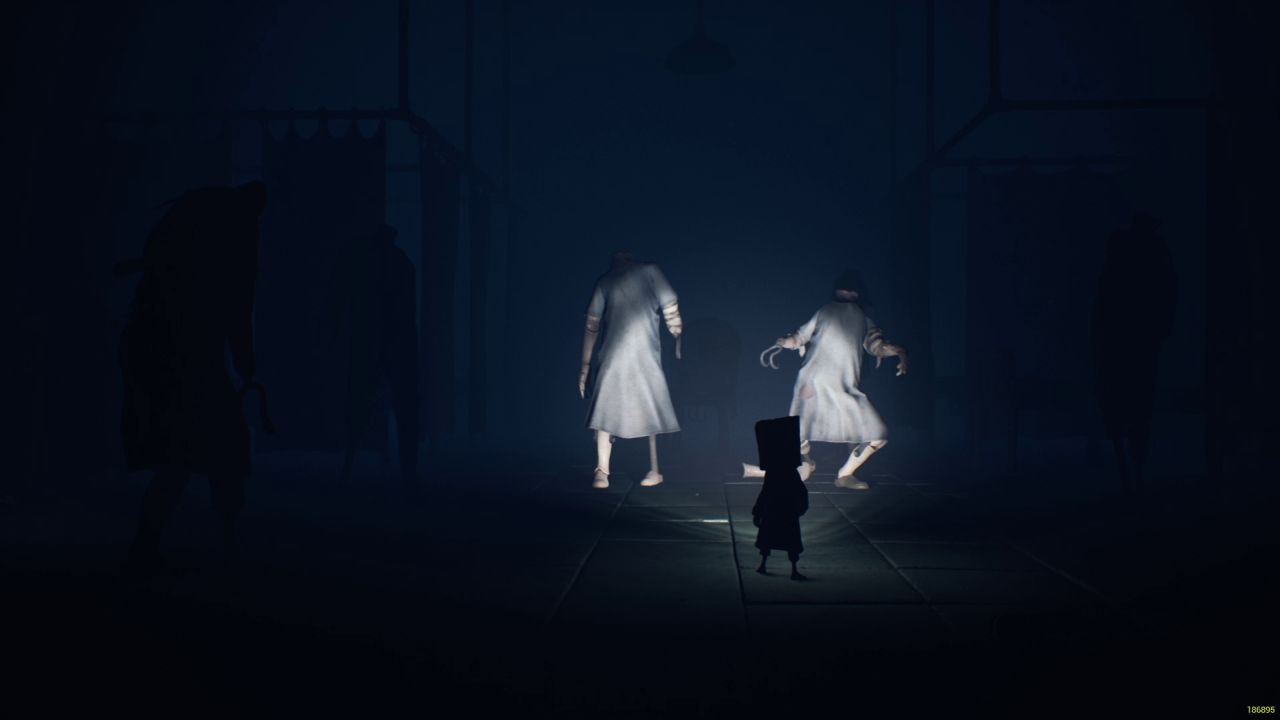 Mono in Little Nightmares 2, in silhouette, shining a light towards to mannequins in blue scrubs.