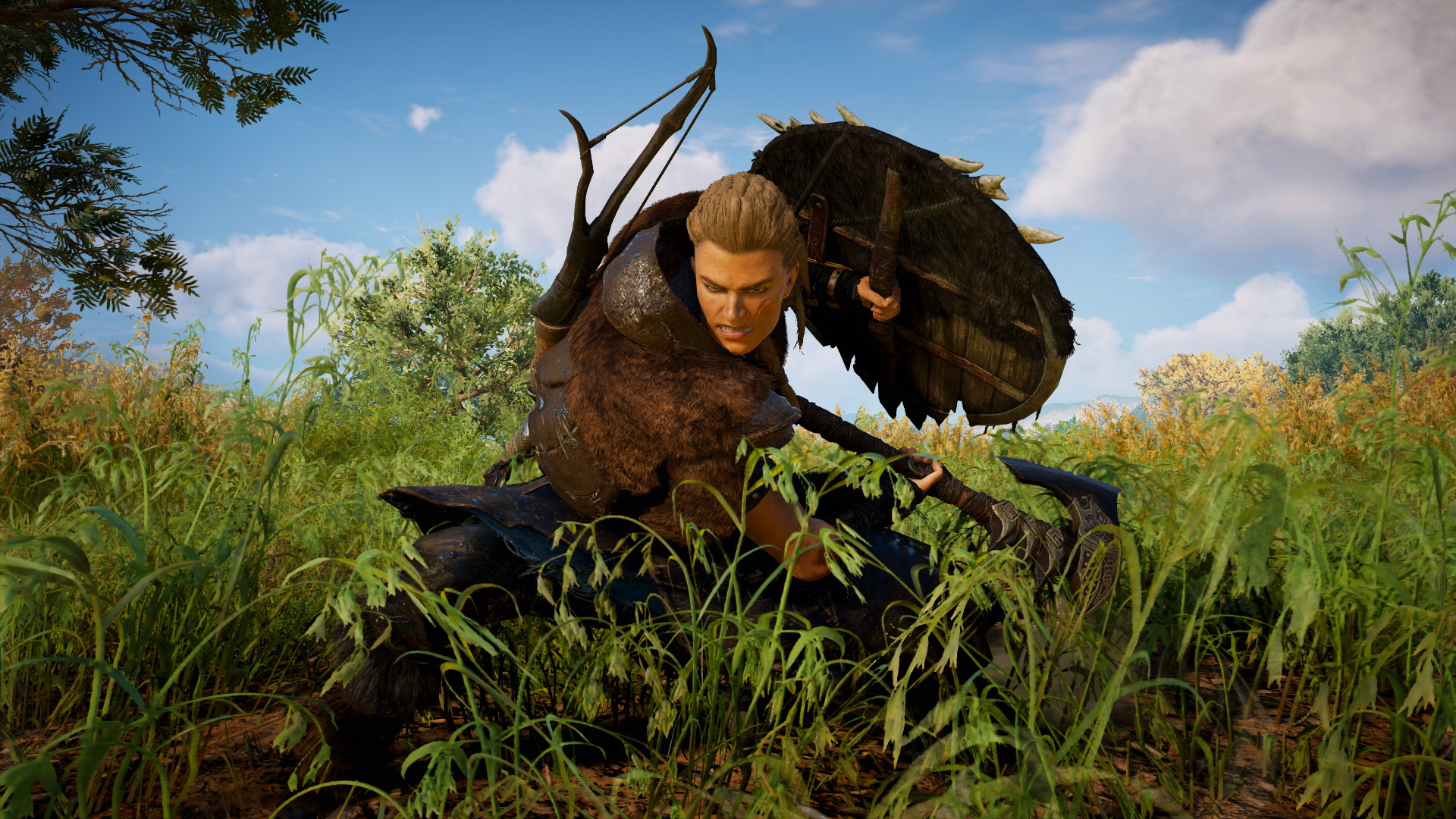 A screenshot of Eivor cutting grass with her axe in Assassin's Creed Valhalla.
