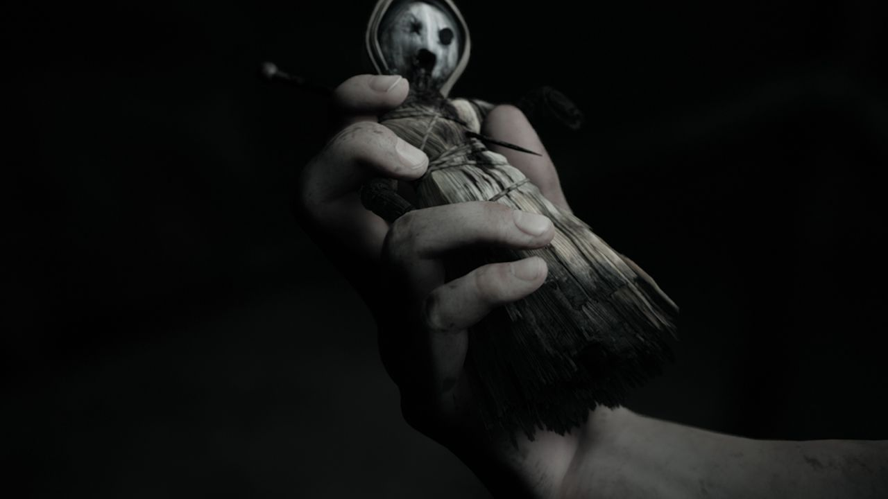 A screenshot from Little Hope showing a close up of a hand holding an extremely creepy corn doll - like, you'd have to make a deliberate effort to make something this disconcerting.