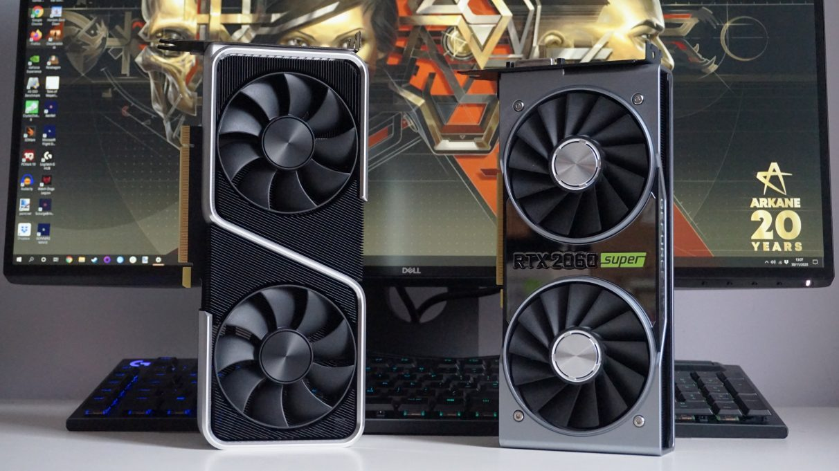 A photo showing the Nvidia GeForce RTX 3060 Ti Founders Edition standing upright next to the RTX 2060 Super Founders Edition in front of a monitor and keyboard.