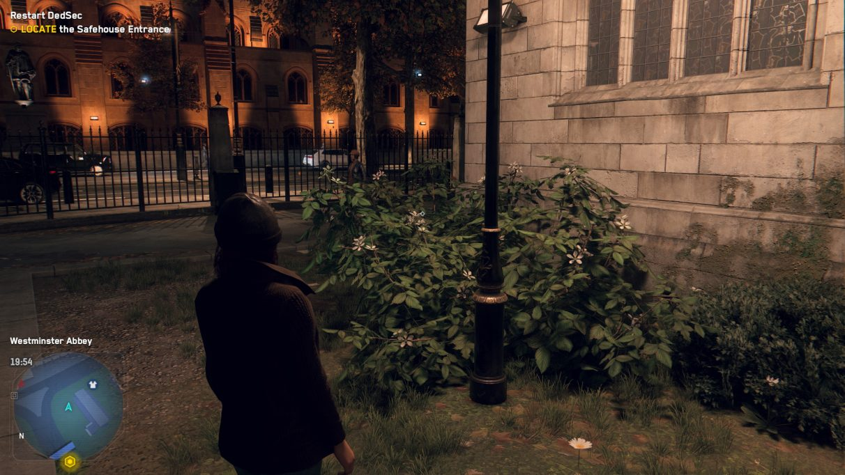A screenshot of a green bush next to a church street lamp at night in Watch Dogs Legion, with Balanced DLSS enabled.