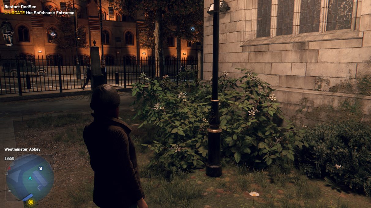 A screenshot of a green bush next to a church street lamp at night in Watch Dogs Legion, with Performance DLSS enabled.