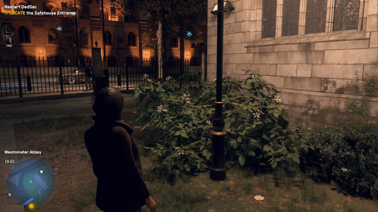 A screenshot of a green bush next to a church street lamp at night in Watch Dogs Legion, with Quality DLSS enabled.