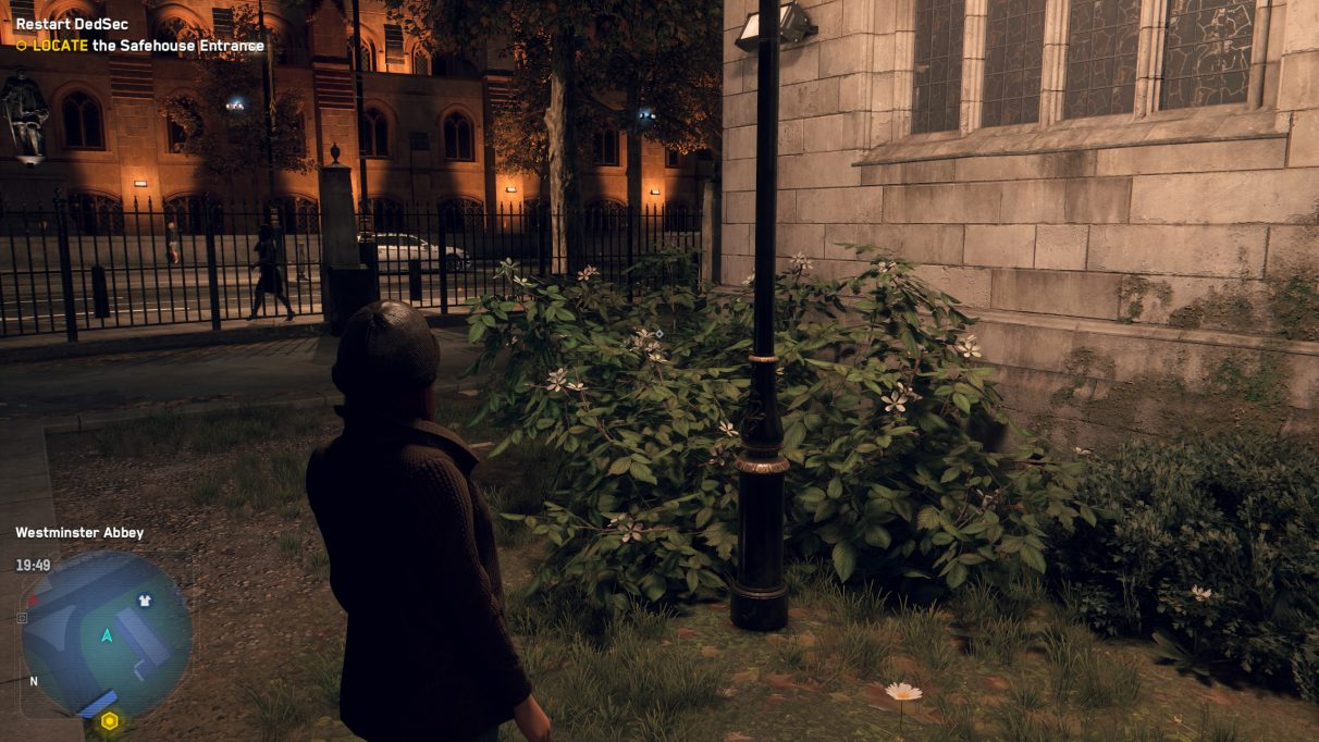 A screenshot of a green bush next to a church street lamp at night in Watch Dogs Legion, with no DLSS enabled.