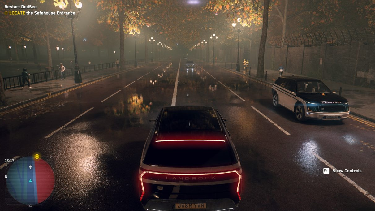 A screenshot of a street at night in Watch Dogs Legion with trees lining the road reflected in the wet puddles on the road.