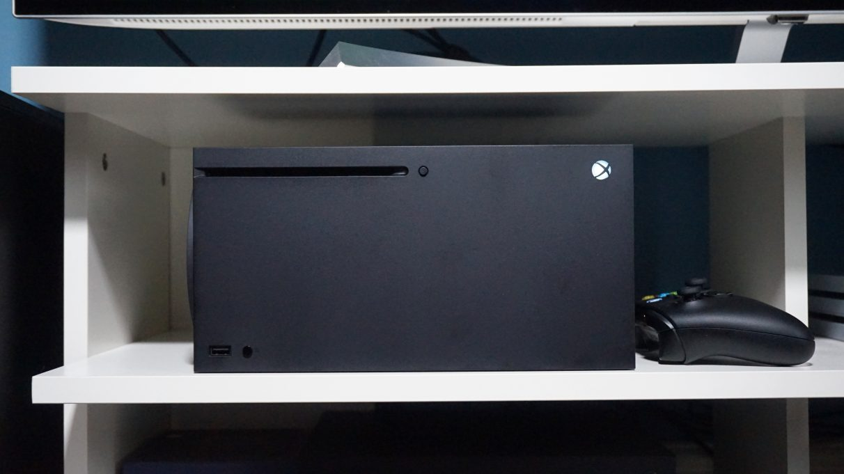 A photo of the Xbox Series X on its side inside a TV cabinet.
