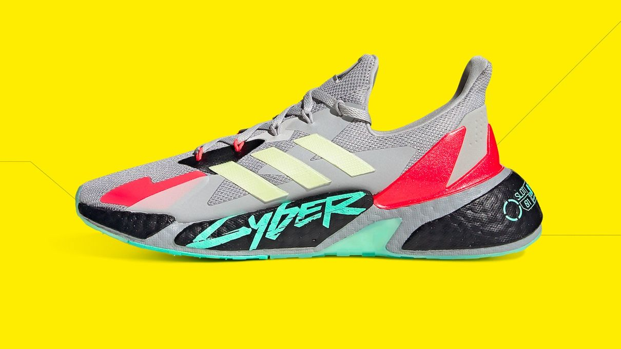A Cyberpunk 2077 Adidas trainer, a nightmare in grey with red and black accents, neon green sole, CYBER written in the same green, and the three Adidas stripes in a grim yellow