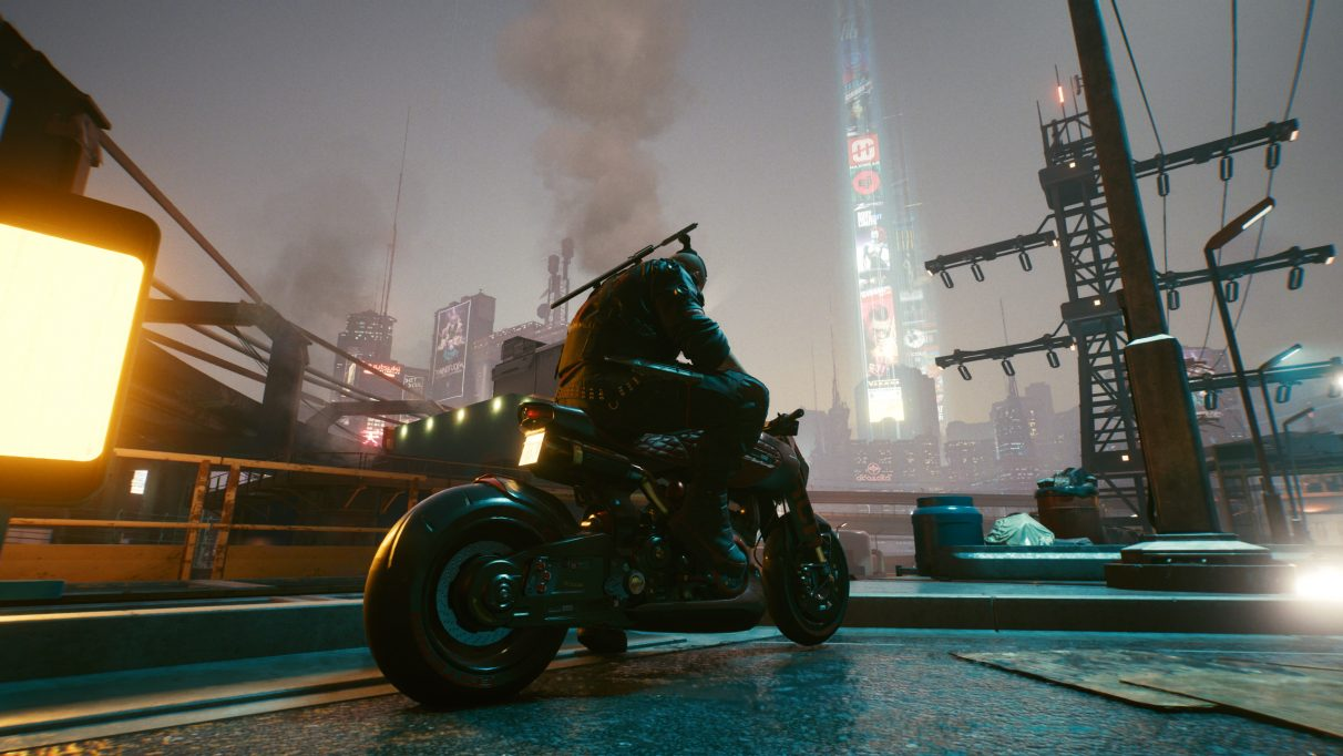 A screenshot of Jackie sitting on his motorbike looking out at the Night City skyline in Cyberpunk 2077