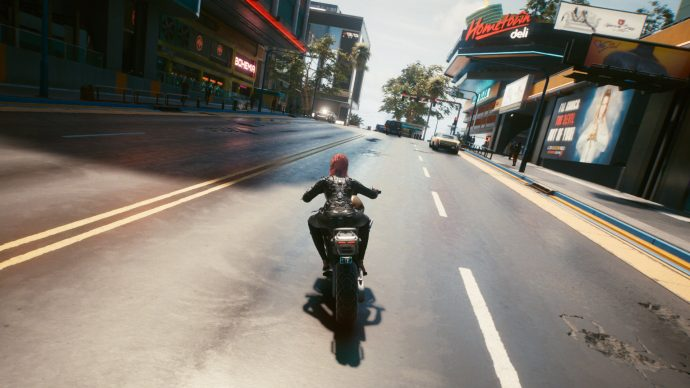 A third-person screenshot of V riding a motorcycle through Night City. Taken using Photo Mode.