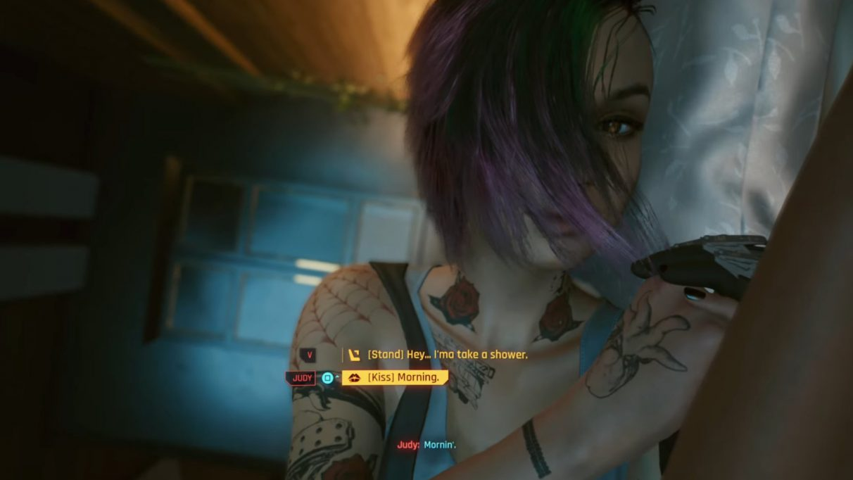 A screenshot of Judy Alvarez in Cyberpunk 2077, waking up next to the player character, V.