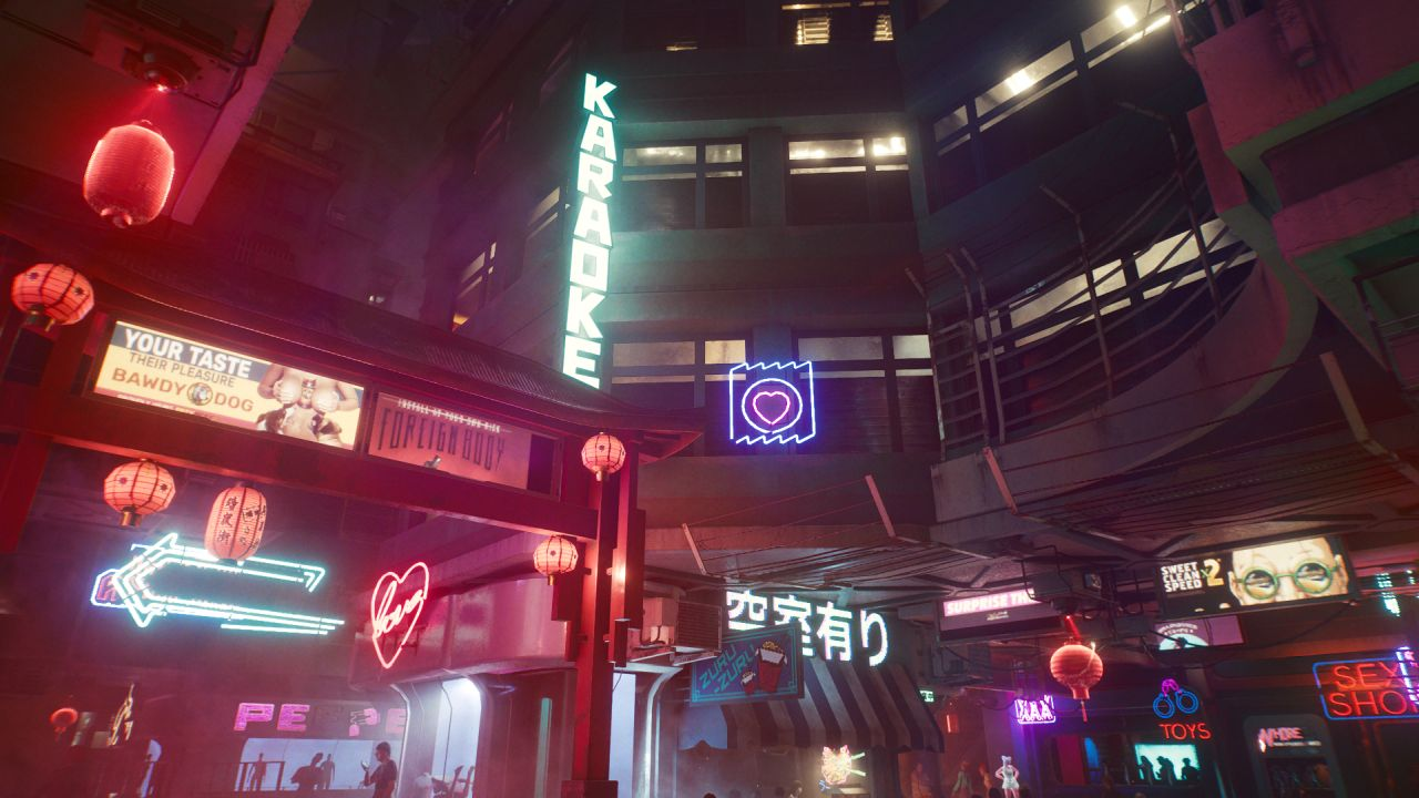 An enclosed street at night. There are many neon signs, some heart shapeds, one reading SEX SHOP and another LOVE, another showing handcuffs with TOYS written underneath.