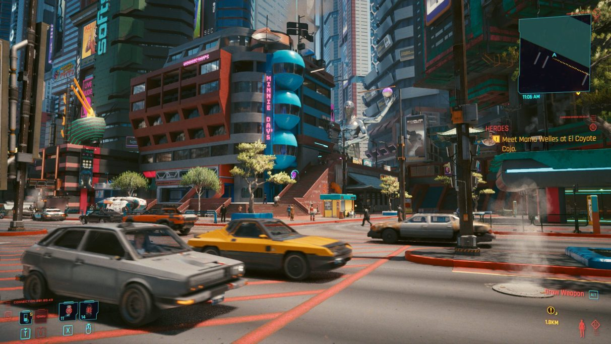 A screenshot of Cyberpunk 2077's Night City, busy with detail. There are cars whizzing by in the foreground, colourful buildings in the distance, and an enormous statue nestled among them.
