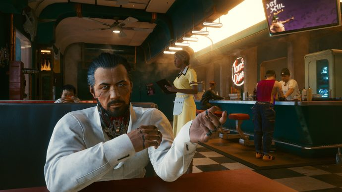 A screenshot of the inside of a diner in Cyberpunk 2077, in which the player is in conversation with Takemura, a Japanese man who is gesturing while he speaks.