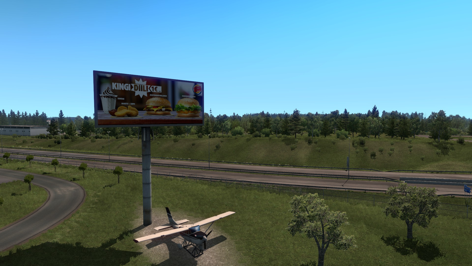 A Euro Truck Sim 2 screenshot showing off a fast food advertisement on a billboard. This is selling Kingi Diili burgers