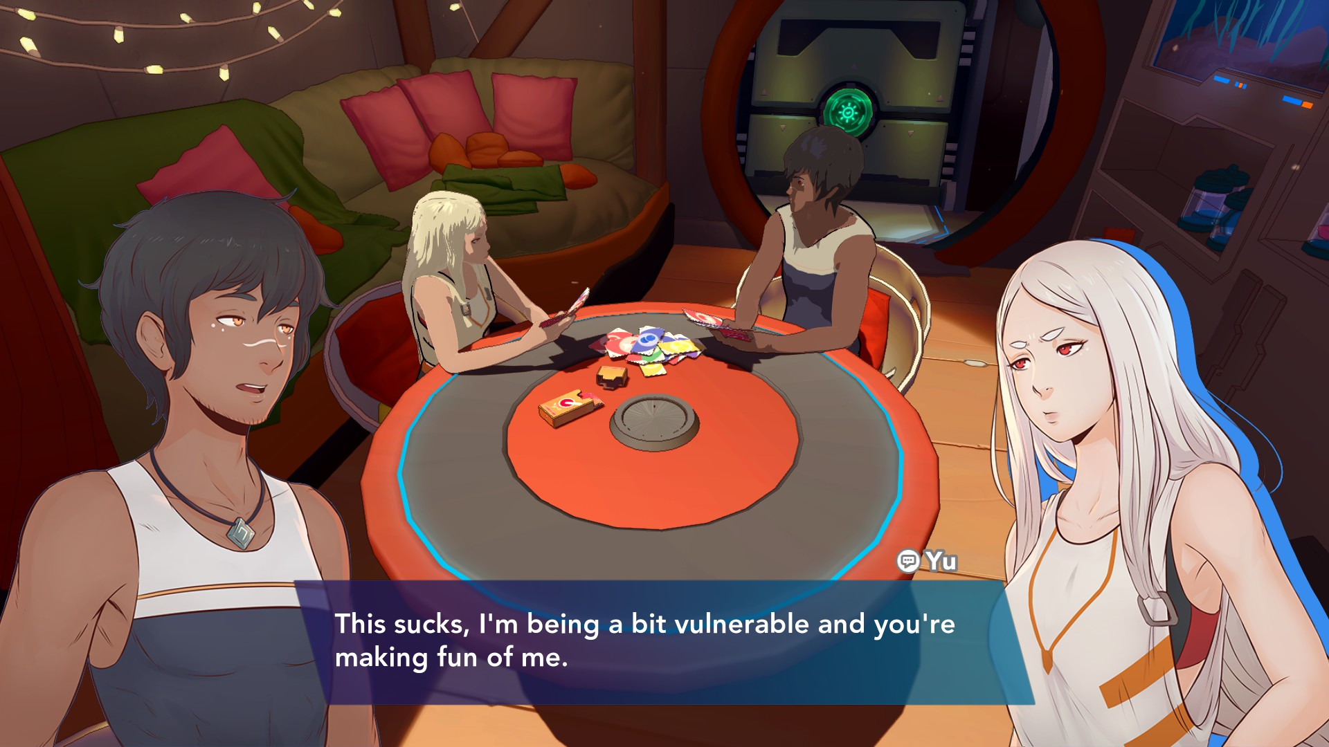 Kay and Yu are sat at the living area table in their spaceship home, playing a card game that looks a bit like Uno. Yu is saying 'This sucks, I'm being a bit vulnerable and you're making fun of me.'