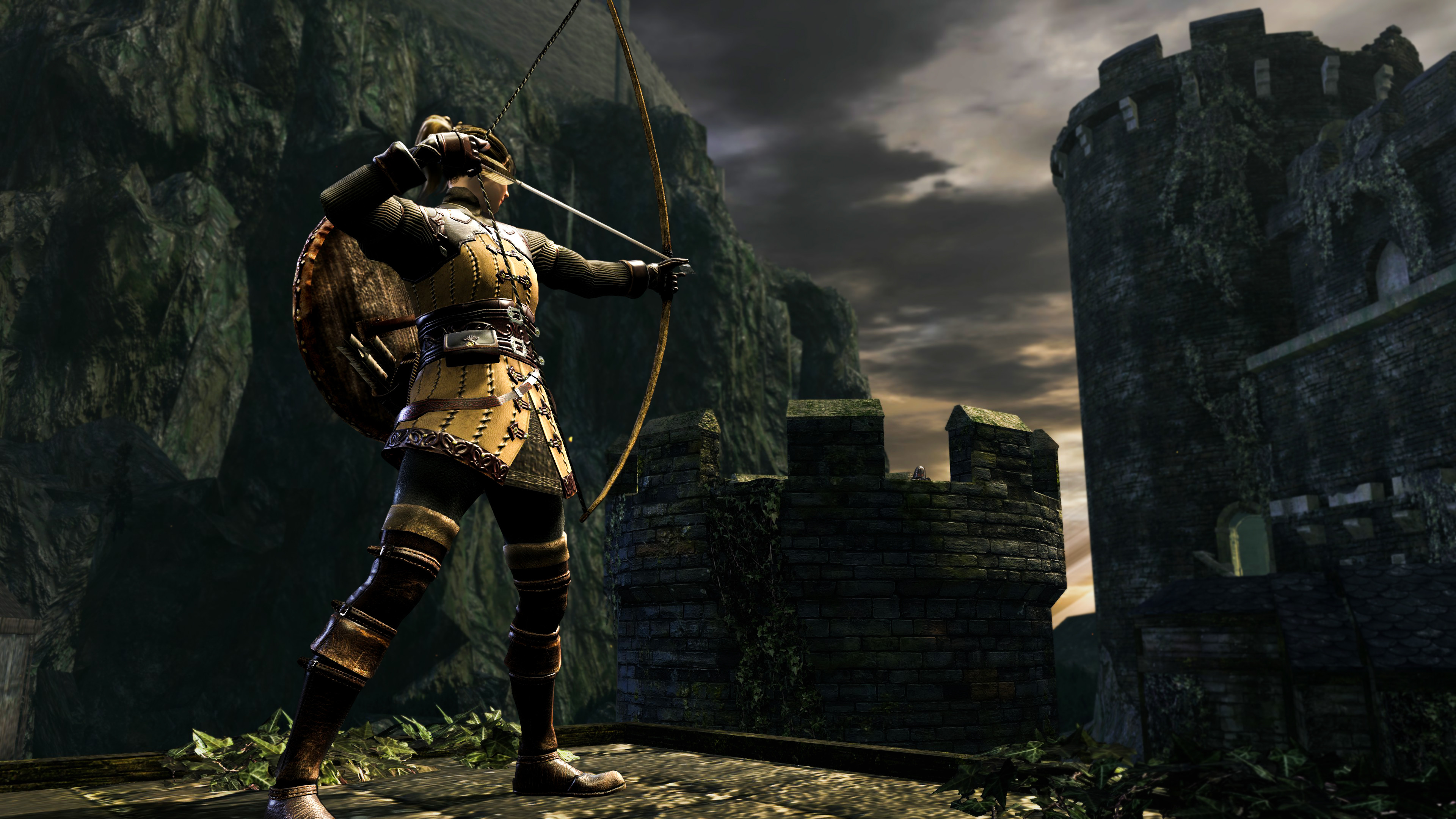 The player character stands, drawing back a long bow, in the Lower Undead Burg of Dark Souls, a collection of European-style castle towers falling to ruin.