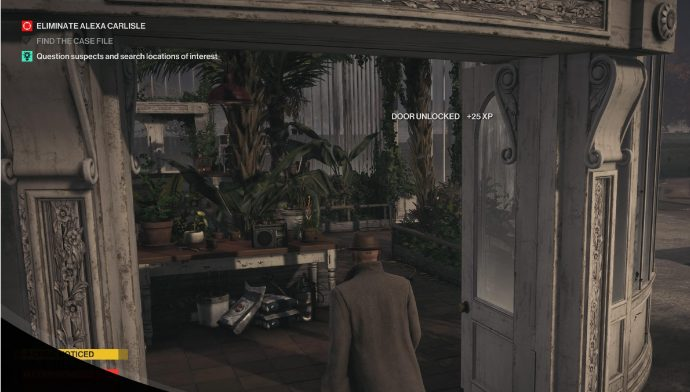 Agent 47 stands in front of the greenhouse in the Dartmoor mission of Hitman 3