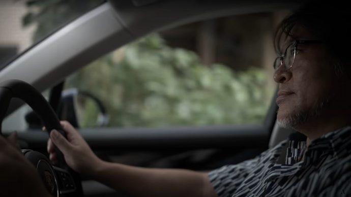A still frame showing Isamu Kamikokuryo driving a car.