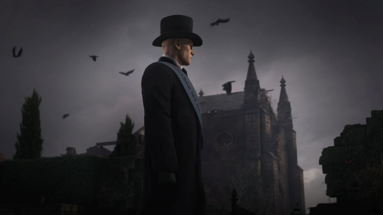 Ian Hitman dressed in a top hat and black coat, with a grey sash reading NEARER MY GOD TO THEE. A lot of ravens are flying around in the sky behind him