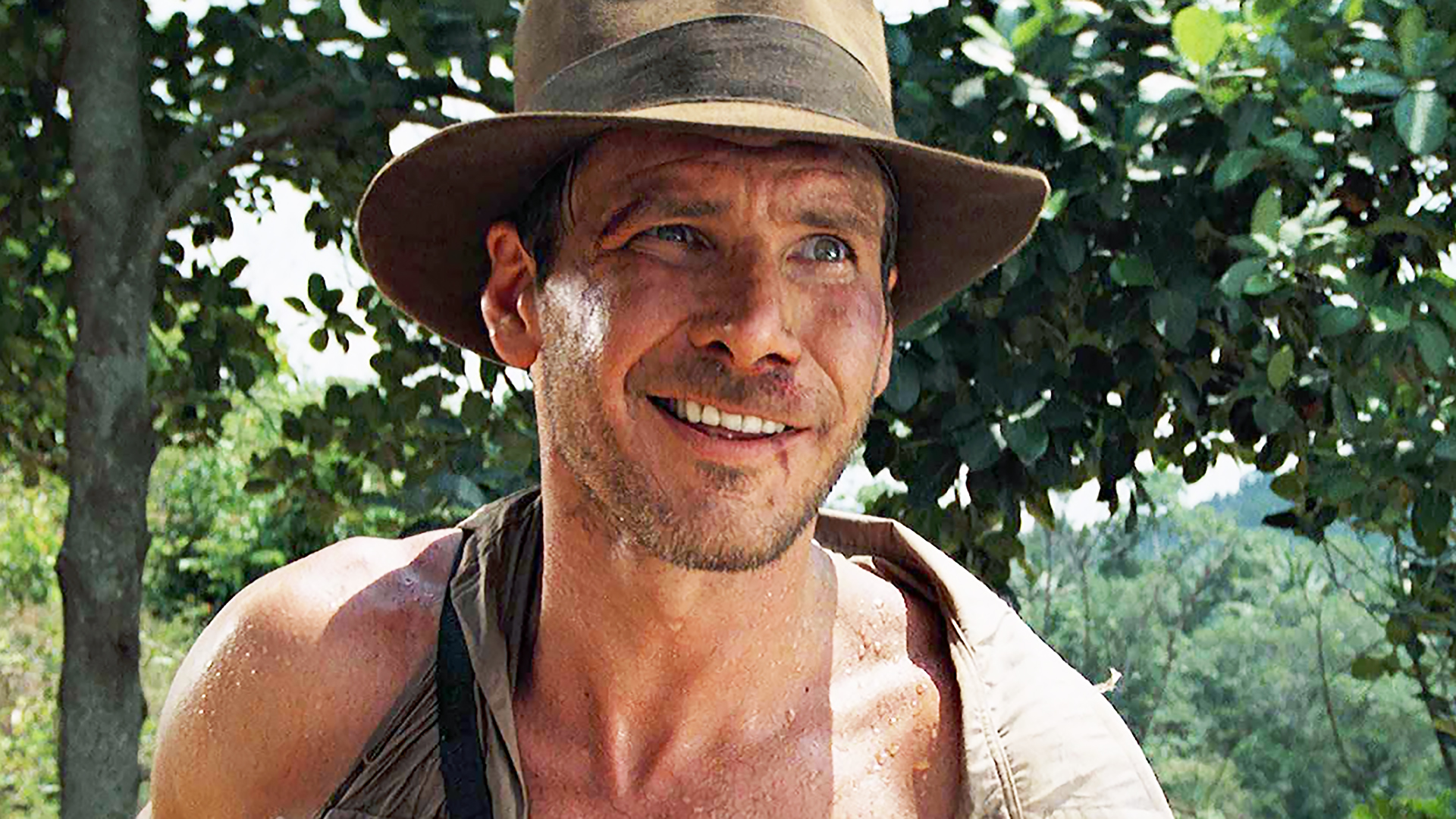 A handsome, young Harrison Ford weirdly smiling while dressed in his Indiana Jones garb