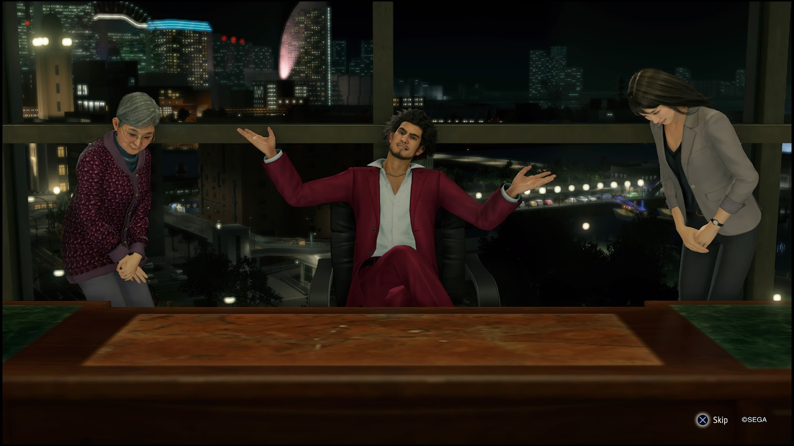 A screenshot of Yakuza: Like A Dragon protagonist Ichiban Kasuga, sitting triumphantly behind a desk