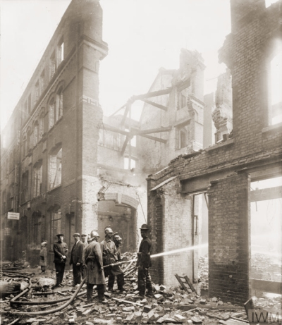 """Firemen hose down the smouldering remains of Cox's Court off Little Britain in the City of London after a Gotha air raid on 7 July 1917"" © IWM (HO 77)"