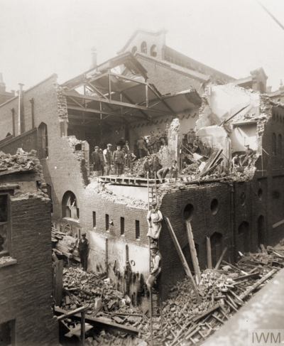 """A general view of the damage caused to buildings on Pancras Road, King's Cross, during the second daylight raid on London by German Gotha GV aircraft on 7 July 1917. A team of soldiers and civilians can be seen on an upper floor of the building, which is open to the elements, the roof having been destroyed in the blast, helping to clear the rubble."" © IWM (HO 76)"